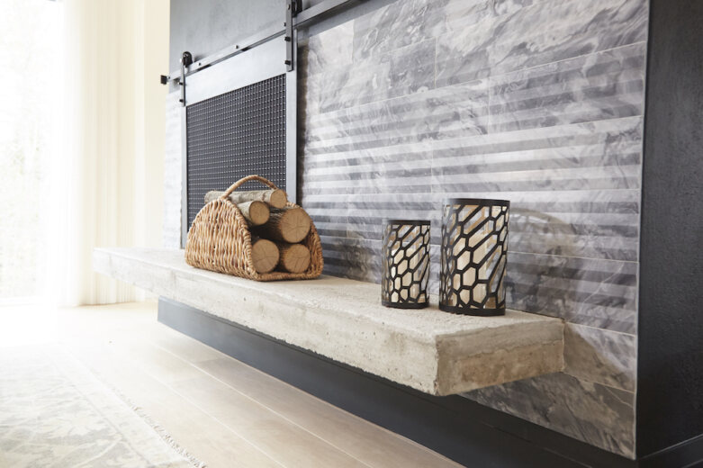 Modern fireplace with a concrete hearth, grey tiles, sliding metal grate, two black hurricane candle holders, and a basket of logs
