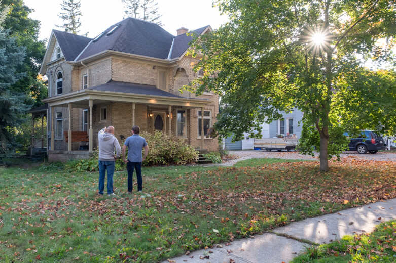 HGTV building experts Bryan Baeumler and Scott McGillivray point to exterior of charming yellow brick Victorian home in Ontario, Canada, as part of HGTV's Home to Win: For the Holidays renovation TV show
