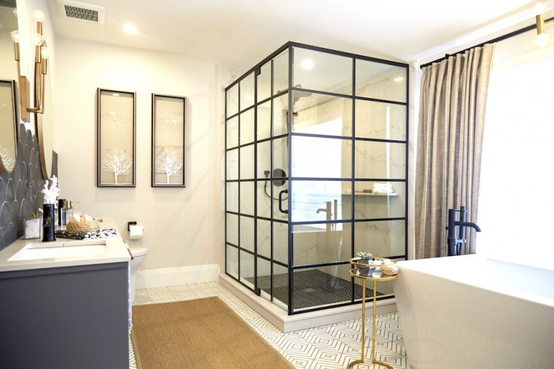 Home to Win Season 3 bathroom with black glass walk-in shower, deep soaker tub and geometric tiled floors