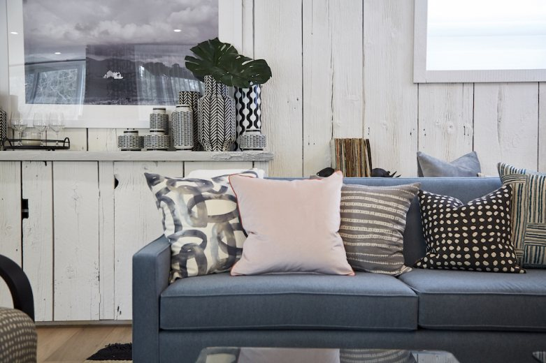 Home to Win Season 3 family room blue couch with black, grey, white and pink throw pillows and grouping of vases sitting on a credenza behind it