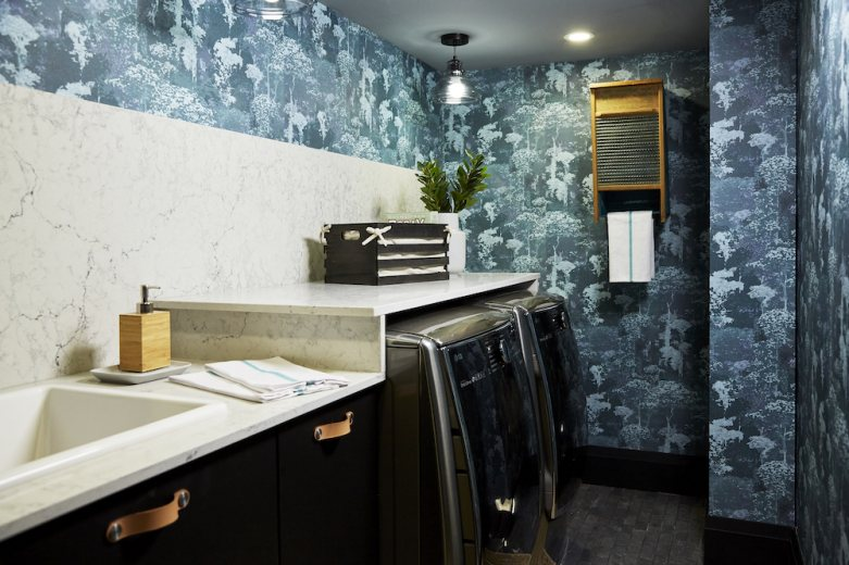 Home to Win Season 3 basement laundry room with a washer, dryer, blue tree-print wallpaper and marble counter tops